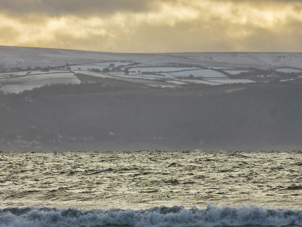 Snowy hills above Minehead, viewed from across the Severn