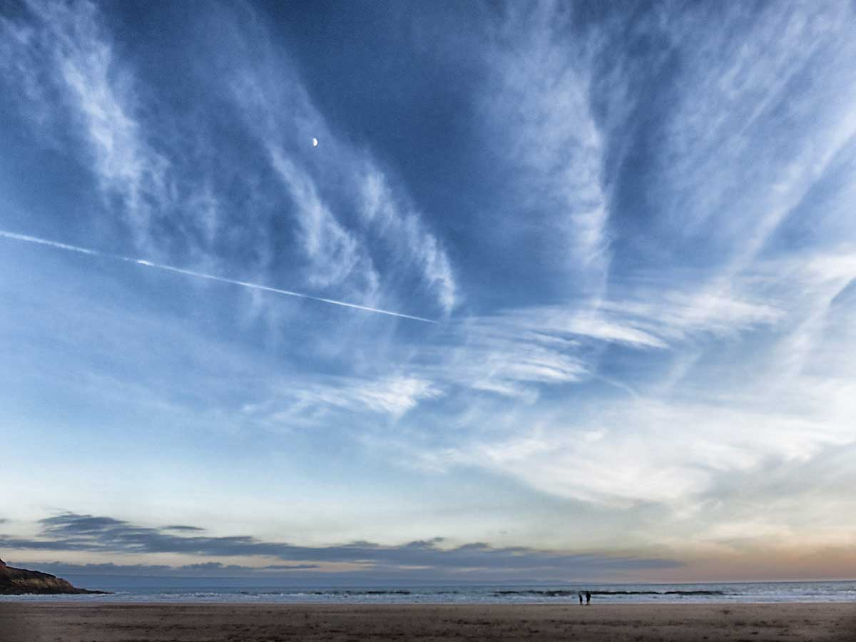 Moon, wavy clouds and contrails over Dunraven Bay