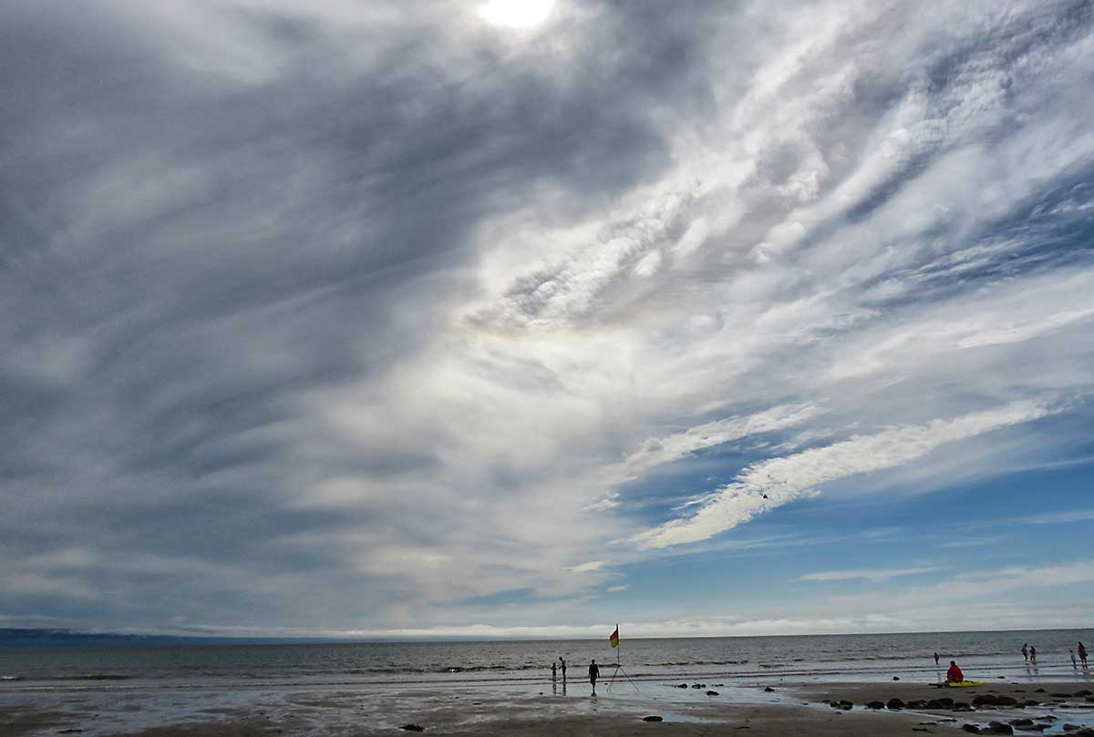 Lifeguard watches the sea as big clouds swirl above, Llantwit Major Beach.