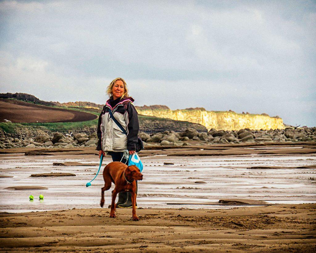 Dog walker and cliffs.