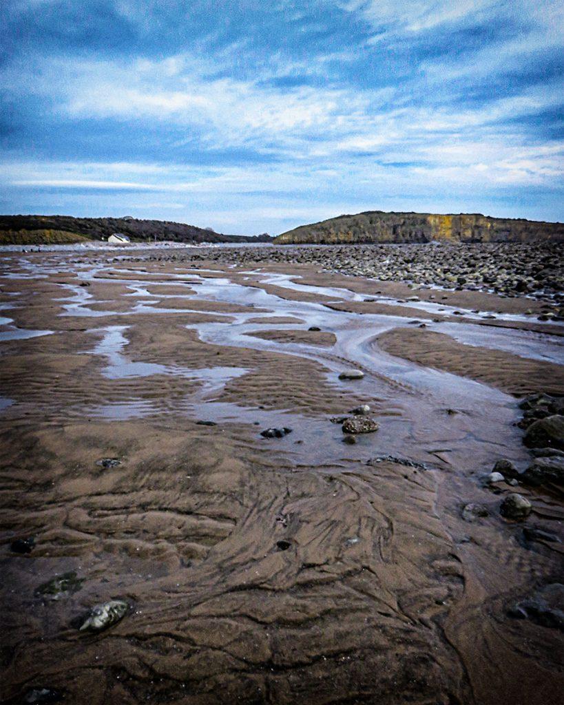 Water running down beach to sea.